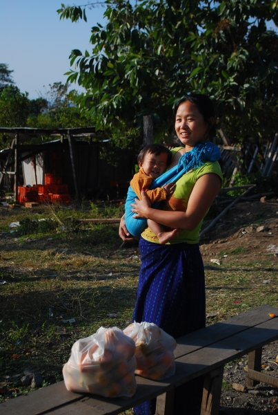 A tribal lady, holding her baby, who has the cutest of smiles; selling some fresh, organic and juicy oranges in front of her house.