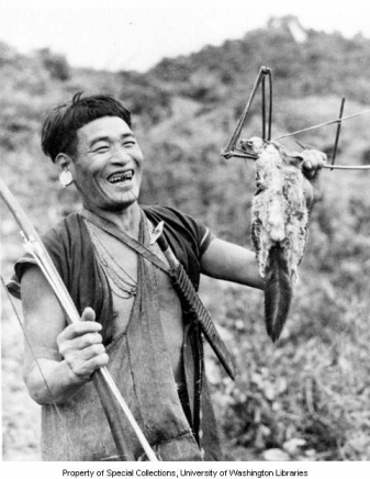 Minyong Adi man with chin tatoo holding bow, arrow and squirrel caught in trap, Ramgong, Siang Frontier Division, India, ca. 1954