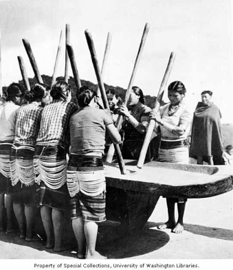 Sema Naga women crushing rice in log mortar with pestles,Tuensang District, Assam, India, ca. 1954